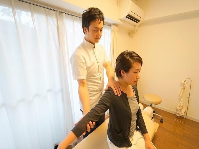 女性の肩の動きを検査する院長