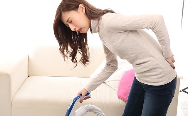 掃除機を持つ腰痛の女性